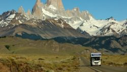 Image: A motorhome is driving on a road in front of a mountain range