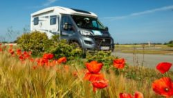 Image: A motorhome is driving along a wheat field