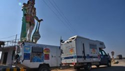 Image: A motorhome with a trailer is parking in front of the statue of an Indian goddess
