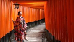 Image: A Japanese woman wearing a kimono is standing in a corridor made of orange beams